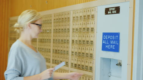 A-Young-Woman-In-Glasses-Throws-A-Few-Letters-In-The-Mailbox-At-The-Post-Office