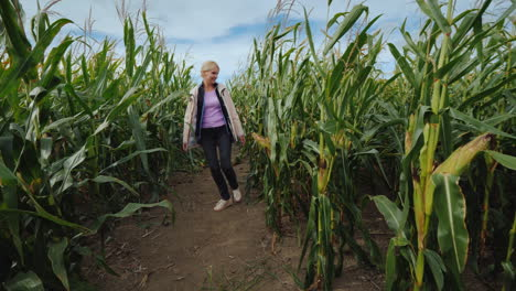 Young-Active-Girl-In-A-Pink-Raincoat-Having-Fun-Among-The-Tangled-Corn-Maze