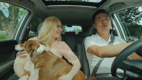Cheerful-Multi-Ethnic-Couple-Riding-In-The-Car-With-A-Big-Dog-In-Her-Arms-Front-View