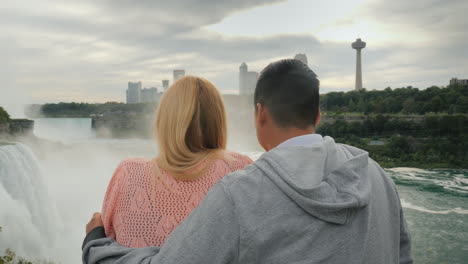 A-Young-Multi-Ethnic-Couple-Looks-At-The-Famous-Niagara-Falls-Enjoying-The-Popular-Tourist-Attractio