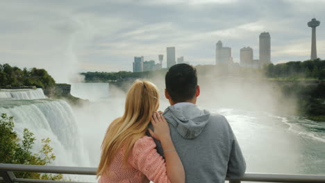 A-Young-Multi-Ethnic-Couple-Admires-A-Beautiful-View-Of-The-Niagara-Falls-Travel-In-America-And-Cana