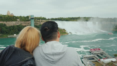 A-Young-Multi-Ethnic-Couple-Of-Tourists-Admire-The-View-Of-The-Famous-Niagara-Falls-From-The-Canadia