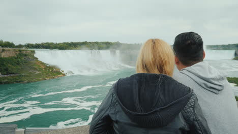 Active-Married-Couple-Spends-A-Weekend-At-Niagara-Falls-Looking-Into-The-Distance-At-The-Cascade-Of-