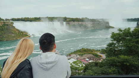 View-From-The-Back-Of-A-Young-Multi-Ethnic-Couple-Looking-At-The-Famous-Niagara-Falls-On-The-Canadia
