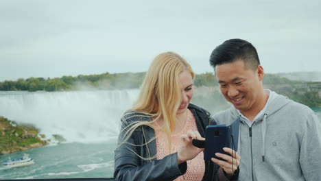 A-Young-Asian-Guy-And-His-Caucasian-Girlfriend-Are-Looking-At-A-Photo-On-A-Telphone-On-The-Observati