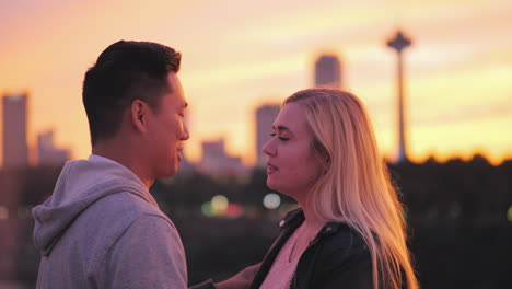 Multiethnic-Young-Couple-Talking-On-The-Bridge-Against-The-Backdrop-Of-A-Big-City-And-A-Beautiful-Su