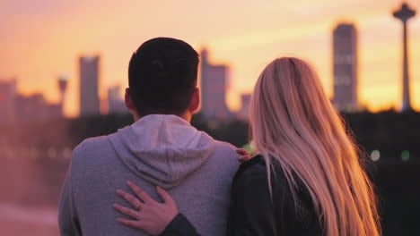 View-From-The-Back-Of-A-Young-Girl-With-Blond-Hair-Hugging-An-Asian-Guy-On-The-Background-Of-The-Sun