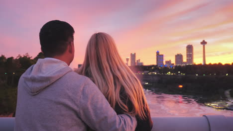 Multi-Ethnic-Couple-Standing-On-A-Bridge-Between-The-Usa-And-Canada-Admiring-A-Beautiful-Sunset