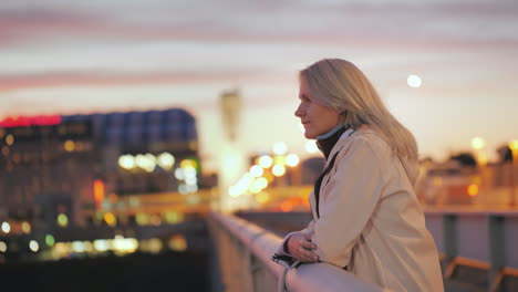A-Young-Woman-Stands-On-A-Bridge-In-A-Night-City-And-Looks-Thoughtfully-Into-The-Distance
