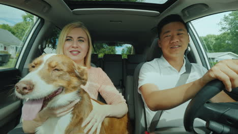 Young-Multinational-Couple-With-A-Dog-Ride-In-The-Car-A-General-Front-View