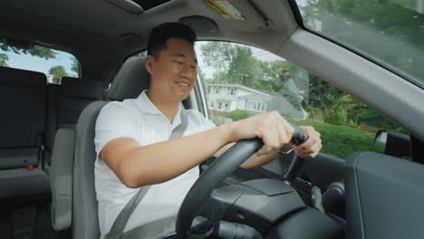 Cute-Asian-Guy-Enjoying-Driving-In-A-Small-American-Town-Front-View