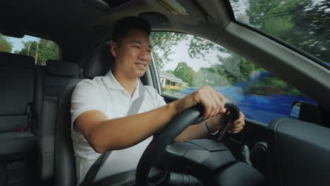 Smiling-Asian-Driver-At-The-Wheel-Of-A-Car-Rides-On-A-Typical-Suburb-Of-The-United-States