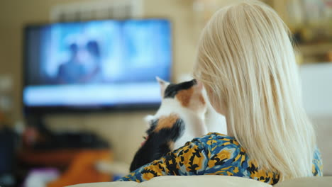 Blonde-Woman-With-A-Kitten-In-Her-Arms-Is-Watching-Tv-Rear-View