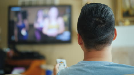 Asian-Man-Watching-Tv-Rear-View