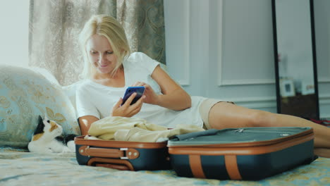 A-Woman-Going-On-Vacation-Uses-A-Smartphone-Around-A-Half-Packed-Travel-Bag
