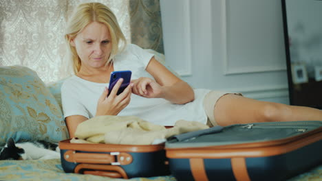 A-Woman-Uses-A-Smartphone-Lies-Next-To-An-Open-Suitcase-With-Clothes