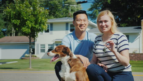 Happy-Multi-Ethnic-Family-With-A-Dog-Against-The-Background-Of-A-New-Home-Holds-The-Key-In-His-Hand