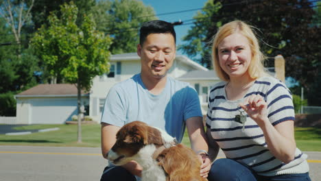 Portrait-Of-A-Family-With-A-Dog-On-The-Background-Of-Their-New-Home-They-Hold-The-Key-In-Their-Hands