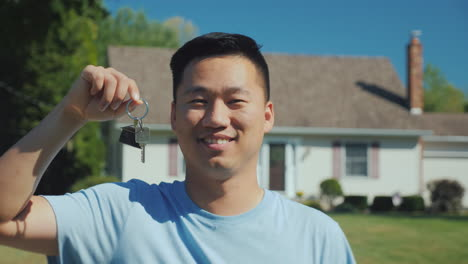Portrait-Of-A-Young-Asian-Man-With-A-House-Key-In-His-Hand-Looking-At-The-Camera-Against-The-Backgro