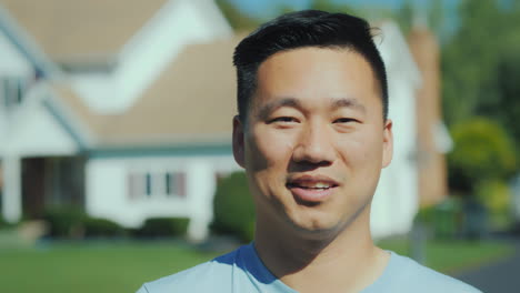 Portrait-Of-A-Young-Asian-Man-Smiling-Looking-At-The-Camera-Against-A-Blurred-Background-At-Home