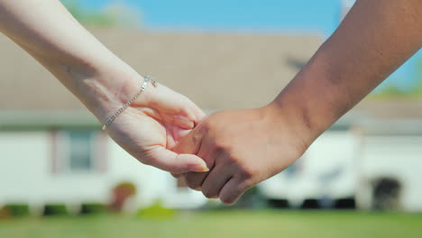 A-Young-Couple-Holding-Hands-Against-The-Backdrop-Of-Their-New-Home-Buying-Real-Estate-Concept-A-Dre