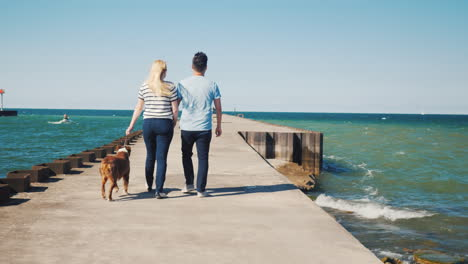 Young-Multiethnic-Couple-Walks-With-A-Dog-On-A-Pier