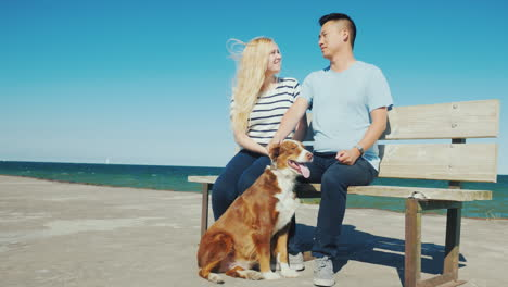 A-Young-Couple-Is-Sitting-On-A-Bench-On-The-Pier-Playing-With-Their-Dog-Walk-With-Your-Pet