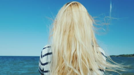 Blonde-Woman-With-Long-Hair-Looks-At-The-Sea-Wind-Ruffles-Her-Hair