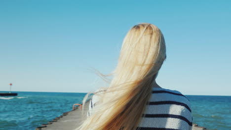 A-Woman-With-Long-Hair-Strolls-Along-The-Pier-The-Wind-Ruffles-Her-Hair-Back-View