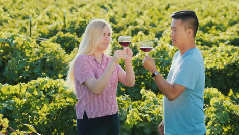 Asian-Man-And-Caucasian-Woman-Tasting-Wine-Near-A-Vineyard-At-A-Small-Winery-Private-Tasting-And-Tou