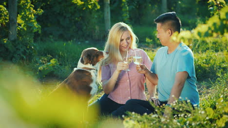 Happy-Couple-Tasting-Wine-Near-The-Vineyard-Their-Dog-Near-Them-Happy-Together-Good-Time-Concept