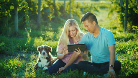 A-Young-Couple-Is-Sitting-Near-A-Vineyard-Using-A-Tablet-Next-To-Them-Is-Their-Dog-Private-Tasting-A