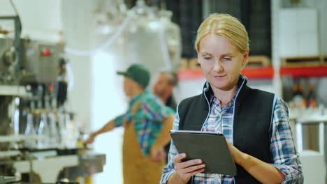 A-Young-Woman-Is-Working-With-A-Tablet-On-The-Background-Of-A-Conveyor-For-The-Production-Of-Beverag