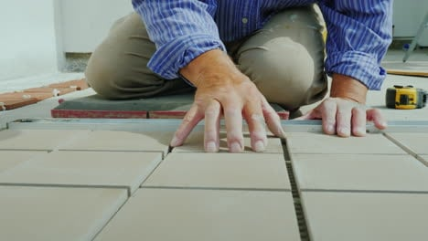 A-Man-Is-Laying-Tiles-On-The-Floor-Only-Hands-Are-Visible-In-The-Frame