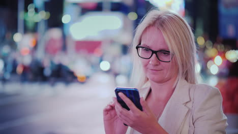 Young-Woman-In-Glasses-Uses-A-Smartphone-On-A-Busy-Street-Of-Manhattan-At-Night
