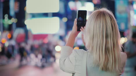 Tourist-Takes-Pictures-With-A-Smartphone-On-The-Famous-Times-Square-In-New-York-Rear-View