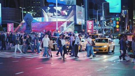 A-Crowd-Of-Pedestrians-Crossing-The-Street-In-Times-Square-Advertising-Lights-Highlight-The-Street