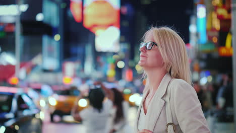 Attractive-Woman-Admiring-The-Lights-Of-The-Famous-Time-Square-In-New-York-Yellow-Cabs-Passing-By---