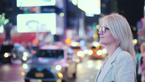 A-Woman-Stands-In-Times-Square-In-New-York-Recognizable-Yellow-Taxis-Are-Passing-By---A-Symbol-Of-Th