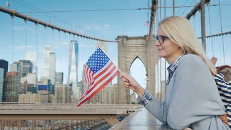 A-Woman-With-The-Flag-Of-America-In-Her-Hand-Stands-On-The-Brooklyn-Bridge-With-A-View-Of-Manhattan-