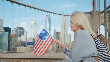Young-Tourist-With-A-Flag-Of-America-And-A-Backpack-Standing-On-The-Brooklyn-Bridge-On-The-Backgroun