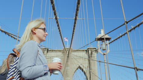 A-Woman-With-A-Cup-Of-Coffee-In-Her-Hands-Is-Standing-On-The-Brooklyn-Bridge-Overlooking-Manhattan-S