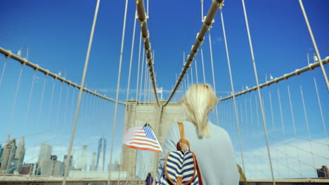 A-Tourist-With-A-Flag-Of-America-And-A-Backpacker-Is-Walking-Along-The-Famous-Brooklyn-Bridge-In-New