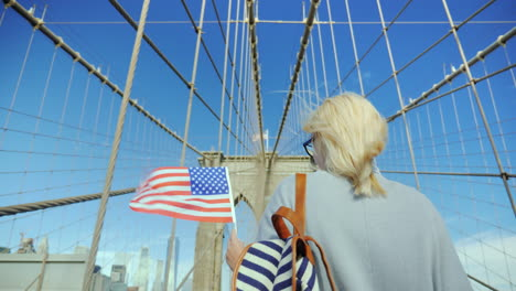 A-Woman-With-The-Flag-Of-America-In-Her-Hand-Is-On-The-Brooklyn-Bridge