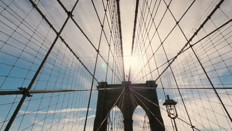Slider-Shot-Of-The-Brooklyn-Bridge-The-Sun-High-In-The-Sky-Will-Light-Above-The-Pillars-Of-The-Bridg