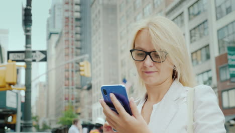 A-Young-Woman-Uses-A-Smartphone-Against-The-Backdrop-Of-Office-Buildings-In-Downtown-Manhattan-New-Y