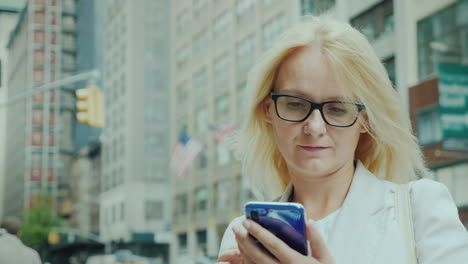 Attractive-Woman-In-Glasses-Is-Looking-At-The-Screen-Of-A-Smartphone-In-The-Background-Are-Tall-Buil
