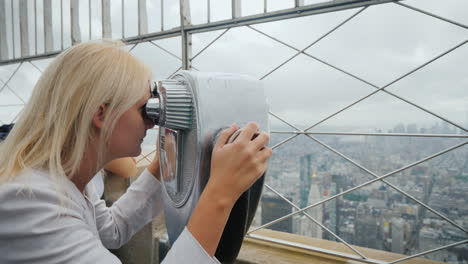 Blonde-Woman-Looking-Through-Binoculars-On-The-Panorama-Of-New-York-Visit-New-York-Concept
