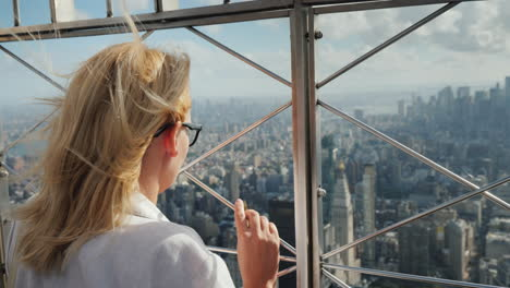 A-Woman-Looks-Down-At-A-Beautiful-View-Of-The-Business-District-Of-Manhattan-It-Stands-At-The-Fence-