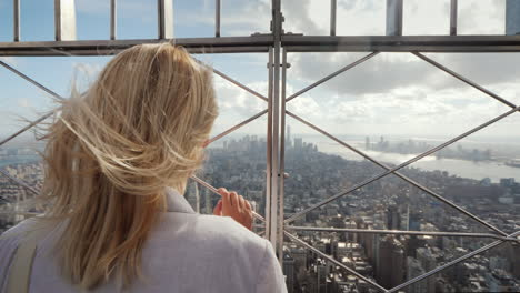 The-Woman-Looks-At-The-Metropolis-Below-It-Stands-At-The-Fence-Rear-View-In-The-Distance-Visible-Sky